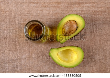 Avocado and avocado oil on wooden background - stock photo