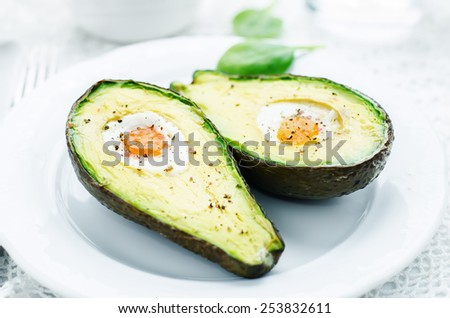 avocado baked with egg on a white background. tinting. selective focus - stock photo