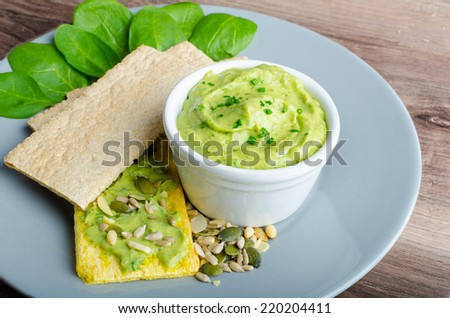 Avocado-Buttermilk Green Goddess Dip with fresh herbs and  Crispbread with a mixture of seeds - stock photo