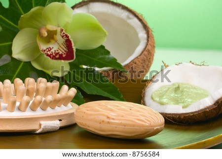 Avocado coconut scrub in coconut shell, orchid flower (Cymbidium sp.), soap and brush. Suited for relaxing and health commercials - stock photo
