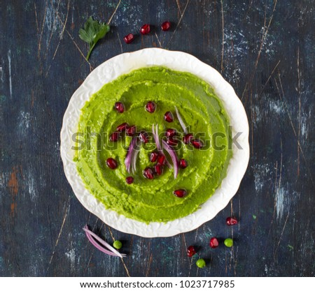 Avocado green pea hummus served with pomegranate and pickled onion.