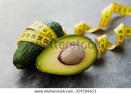 Avocado half and whole with tape measure on black background, diet concept - stock photo