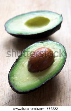 Avocado halves on a chopping board