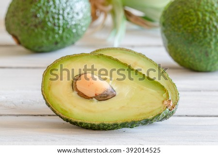Avocado in a kitchen on a wooden desk - stock photo