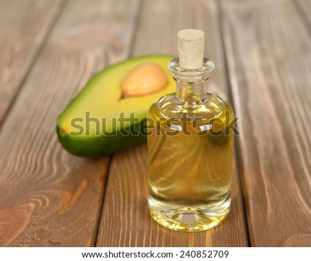 Avocado oil on a brown background - stock photo
