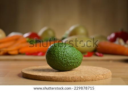 Avocado on the wooden table with different vegetables on the background - stock photo