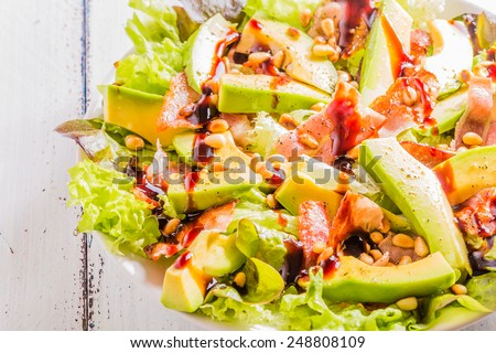 Avocado salad with fried bacon and pine nuts on a white wooden background