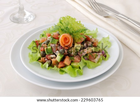 Avocado salad with tomatoes, smoked salmon and capers - stock photo