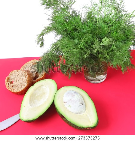 Avocado, sliced rye bread and dill ready for healthy breakfast on a bright color cutting desk. Isolated on white - stock photo