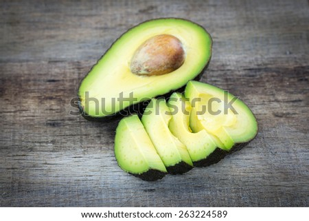 avocado slices on a wood background - stock photo