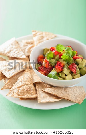 avocado strawberry salsa with tortilla chips - stock photo