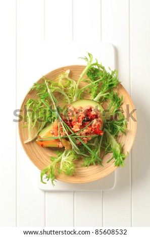 Avocado stuffed with minced meat garnished with salad greens  - stock photo
