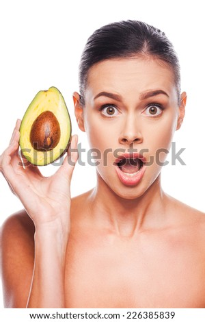 Avocado? Surprised young shirtless woman holding avocado in her hand and keeping mouth open while standing against white background