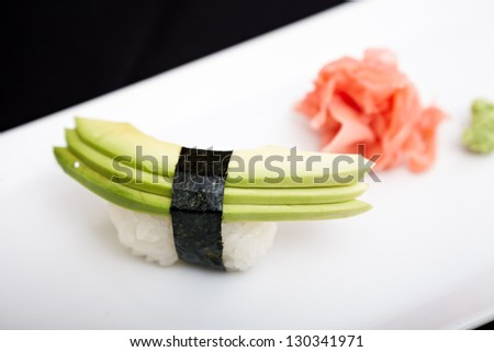 Avocado sushi served on a plate with ginger and wasabi - stock photo
