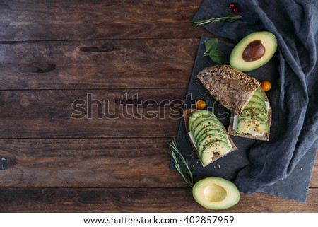 Avocado toast on wooden background. Breakfast with toast avocado, vegetarian food, healthy diet concept. Copy space - stock photo