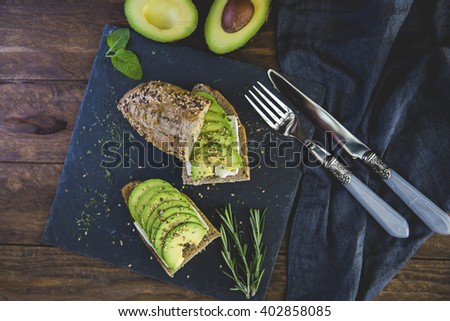 Avocado toast on wooden background. Breakfast with toast avocado, vegetarian food, healthy diet concept. - stock photo