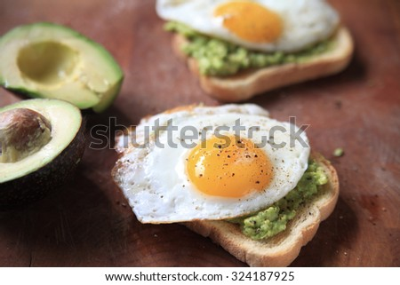 Avocado toast topped with a fried egg and black pepper - stock photo