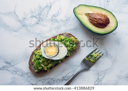 Avocado toast with boiled egg on marble background. Perfect simple healthy breakfast. - stock photo