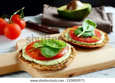 Avocado toast with tomato and spinach on whole grain round flat bread - stock photo