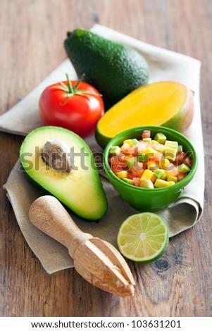 Avocado, tomato, mango salad with lime dressing, selective focus - stock photo