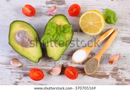 Avocado with ingredients and spices to avocado paste or guacamole, garlic, lemon, cherry tomatoes, basil, concept of healthy food, nutrition and omega fatty acids - stock photo