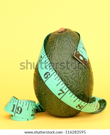 avocado with measuring tape on yellow background