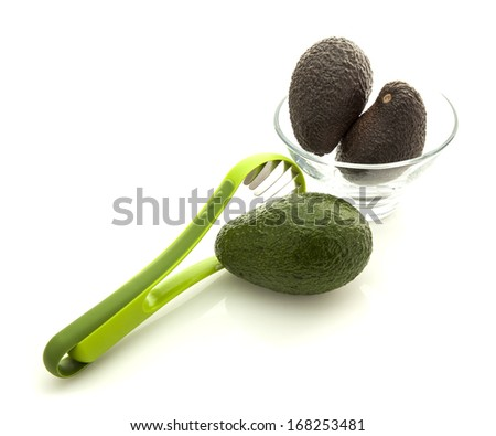 Avocados in glass bowl with slicer isolated on white background