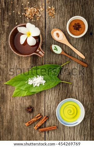 Avocados  leaves with nature spa ingredients cinnamon powder ,cinnamon sticks ,aromatic oil ,star anise  and sea salt on rustic background. - stock photo