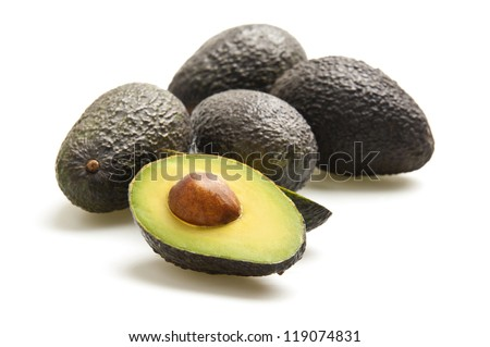 Avocados, one cut in half, photographed on a white background. - stock photo