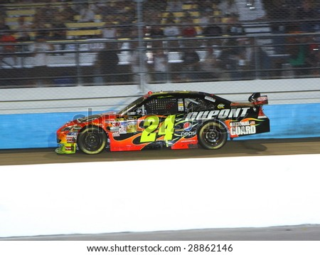 AVONDALE, AZ - APRIL 18: Jeff Gordon (24) works the DuPont Chevrolet through turn one of the NASCAR Sprint Cup Series race at Phoenix International Raceway on April 18, 2009 in Avondale. - stock photo