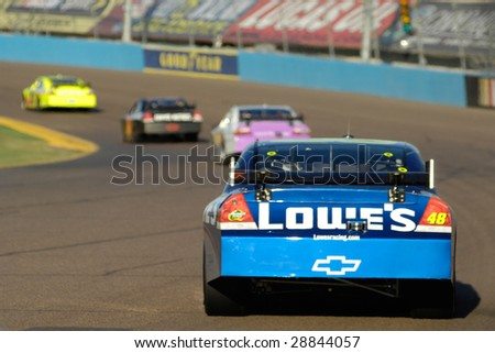 AVONDALE, AZ - APRIL 18: Jimmie Johnson #48 follows a group of cars into turn 3 at the NASCAR Sprint Cup race at the Phoenix International Raceway on April 18, 2009 in Avondale, AZ. - stock photo