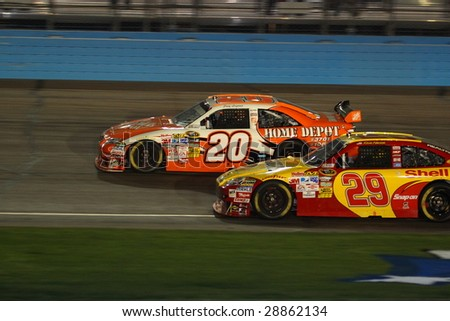 AVONDALE, AZ - APRIL 18: Joey Logano (20) and Kevin Harvick (29) battle it out in turn one of the NASCAR Sprint Cup Series race at Phoenix International Raceway on Saturday, April 18, 2009 in Avondale. - stock photo