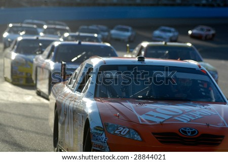 AVONDALE, AZ - APRIL 18: Joey Logano #20 leads a group of cars at the NASCAR Sprint Cup race at the Phoenix International Raceway on April 18, 2009 in Avondale, AZ.