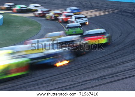 AVONDALE, AZ - NOV 14: Abstract motion-blur of cars at speed in the Kobalt Tools 500 race on Nov 14, 2010 at the Phoenix International Raceway in Avondale, AZ. - stock photo