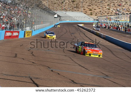 AVONDALE, AZ - NOV. 14: Jeff Gordon (24) and Michael Waltrip (55) take laps during practice for the NASCAR Sprint Cup race, at Phoenix International Raceway on Nov. 14, 2009 in Avondale, AZ. - stock photo