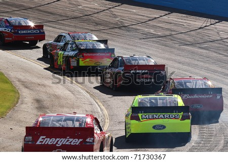 AVONDALE, AZ - NOV 14: NASCAR Sprint Cup cars in turn one during the Kobalt Tools 500 race on Nov 14, 2010 at the Phoenix International Raceway in Avondale, AZ. - stock photo