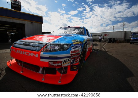 AVONDALE, AZ - NOVEMBER 13: A.J. Allmendinger waits in his car for a practice session for the NASCAR Sprint Cup Series, at Phoenix International Raceway on November 13, 2009 in Avondale, AZ. - stock photo