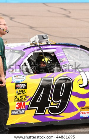 AVONDALE, AZ - NOVEMBER 14: Mark Green (49) buckles in to qualify for the NASCAR Nationwide Series, Able Body Labor 200 at Phoenix International Raceway on November 14, 2009 in Avondale, AZ. - stock photo