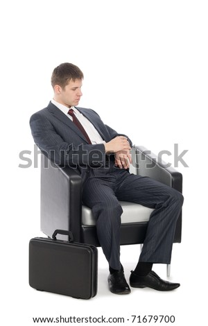 Awaiting a young businessman checking the time on his wristwatch. - stock photo