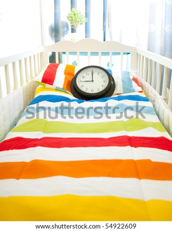 Awaiting baby - bed in nursery room with clock as time concept - stock photo