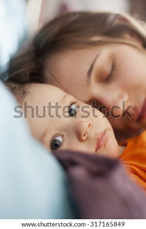 Awake Baby Boy With Mother Sleeping In The Background. Focus Is On Baby. - stock photo