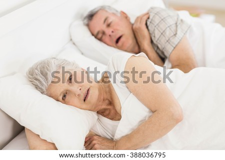 Awake senior woman in bed while her husband is snoring - stock photo