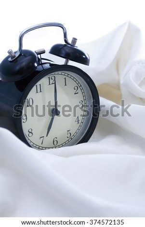 Awakening concept. Black alarm clock on white sheet in bed