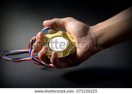 Award of victory. Hand holding blank gold medal on black background  - stock photo