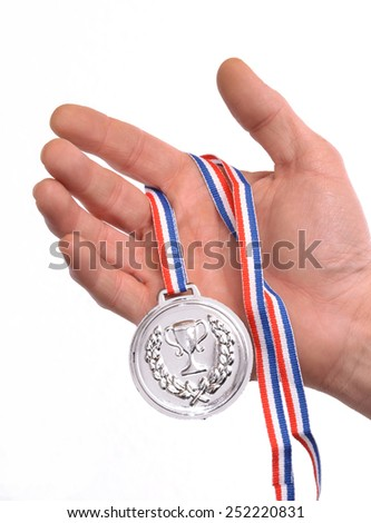 Award winner hand holding a silver medal isolated on white background. - stock photo