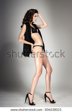 Awesome attractive sexy fashion model with natural brunette hair, long legs, full lips, perfect skin posing in studio, wearing black shoes, lingerie and jacket, beauty photoshoot, retouched image - stock photo