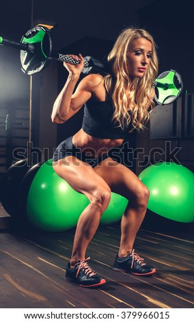 Awesome blond woman in a sexy sportswear doing exercises in a gym.