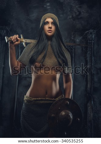 Awesome brunette woman in knight clothes holds shield and sword. - stock photo