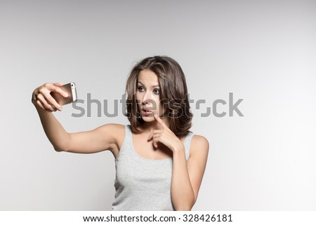 Awesome Caucasian attractive female model with brunette hair is grimacing in studio, making selfies on mobile phone camera, wearing grey shirt and jeans, white background - stock photo