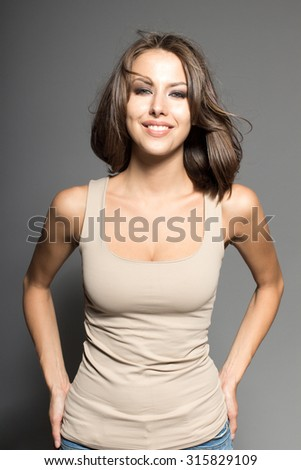Awesome Caucasian attractive joyful happy sexy female model is shaking head with brunette hair, grimacing in studio, wearing beige sleeveless shirt, isolated on gray background - stock photo